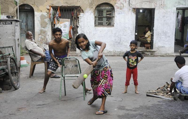 girl playing street cricket kreedon