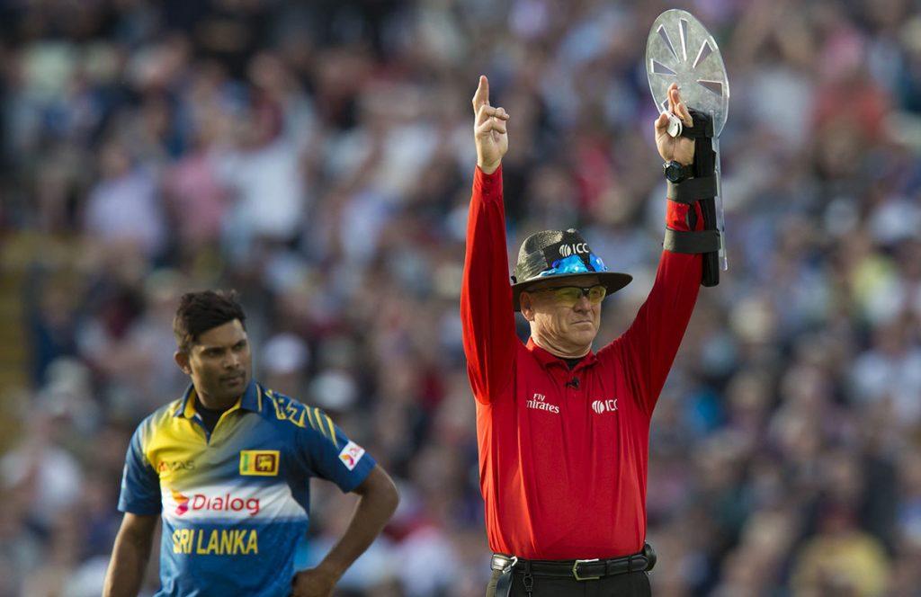 Umpire signalling a six